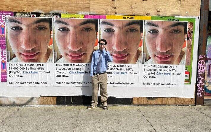 """Ezra Ripps vor Plakaten, auf denen er die """"Million Token Website"""" bewirbt"""